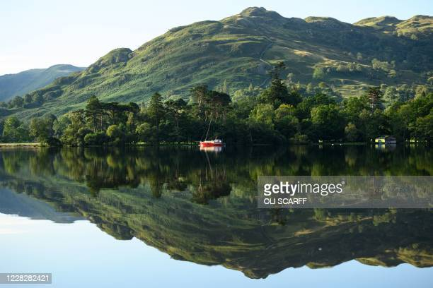 Boats are reflected in the early morning sunshine on Ullswater near Glenridding in the Lake District in north west England on Bank Holiday Monday,...