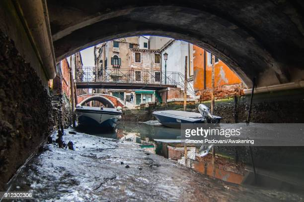 Boats are stucked in low tide in a canal on January 30 2018 in Venice Italy An exceptional low tide affected Venice this afternoon creating problems...