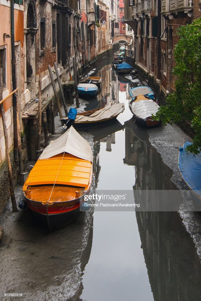 Boats are stucked in low tide in a canal on January 30, 2018 in Venice, Italy. An exceptional low tide affected Venice this afternoon creating problems in transport and navigation.