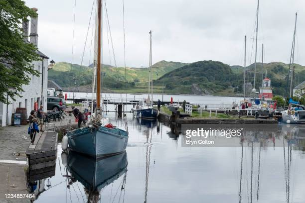 Boats arrive at the sea locks from Loch Crinan and the entrance to the Crinan Canal on August 19, 2021 in Crinan, Scotland. Passage along the canal...