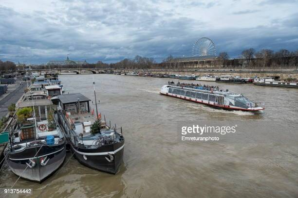 boats at seine riveron an overcast day in paris. - emreturanphoto stock pictures, royalty-free photos & images