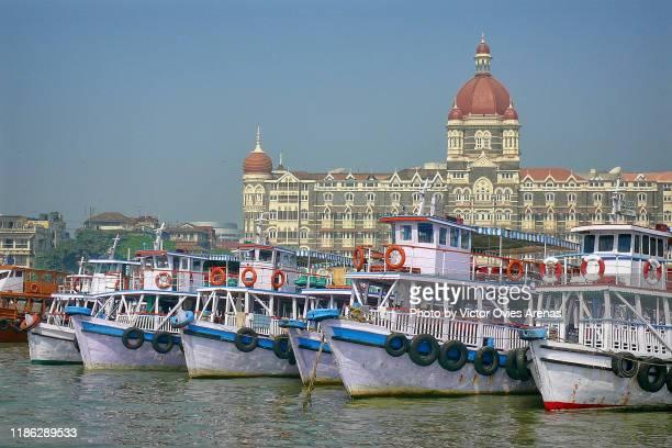 boats at wellington pier (former apollo bunder) seen from the sea and the taj mahal palace in the background in mumbai, maharashtra, india - victor ovies fotografías e imágenes de stock