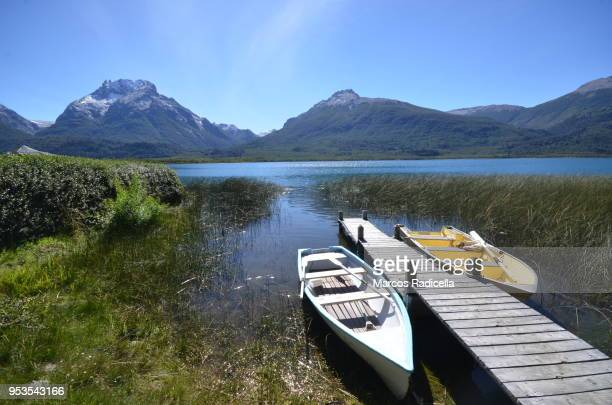 boats by the lake at patagonian lake - radicella stock photos and pictures
