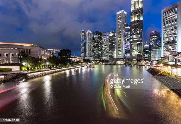 boats, captured with blurred motion, rush along the singapore river at night - didier marti stock photos and pictures