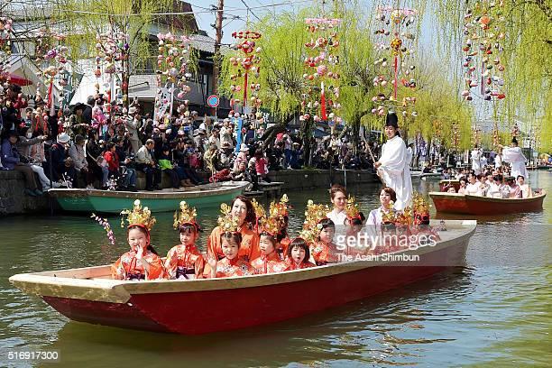 Boats carrying girls wearing traditional kimono cruise a canal during the Hina Matsuri River Parade on March 20 2016 in Yanagawa Fukuoka Japan