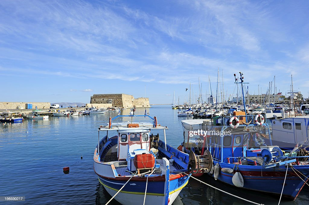 Boats docked in the blue waters of Iraklion : Stock Photo