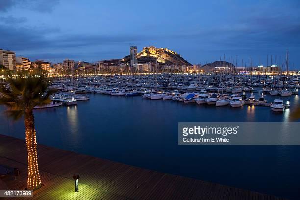 Boats docked in urban harbor at night