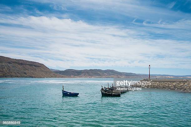 Boats docked on rocky pier in remote harbor