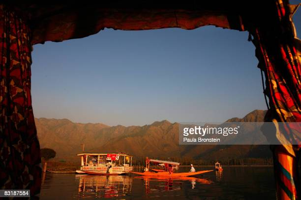 Boats float along Dal Lake seen through the curtain of a tourist paddle boat October 4 2008 in Srinagar Kashmir In the past few months the region's...