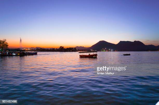 Boats floating on a lake at sunset with blue water and mountains in the distance