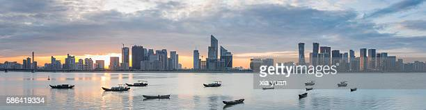 Boats floating on Qiantang River against downtown skyline at sunset,Hangzhou,China