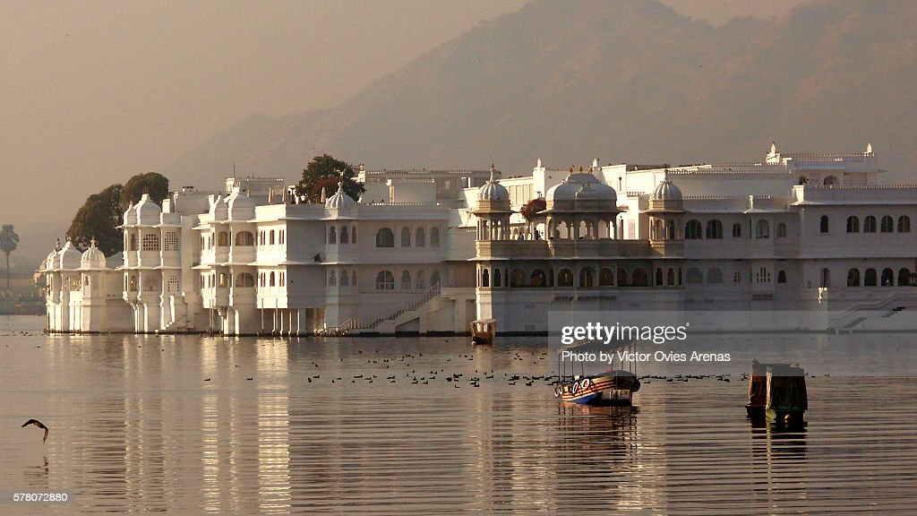 Boats floating placidly in front of the Lake Palace in Udaipur, Rajasthan, India : Stock Photo