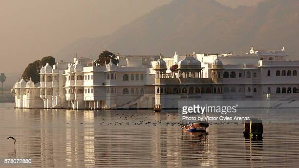 Boats floating placidly in front of the Lake Palace in Udaipur, Rajasthan, India