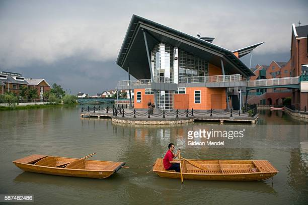 Boats for tourists are paddled into position in front of the harbour in the riverside part of Thames Town a recently constructed typical English...