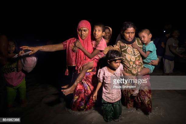 Boats full of people continue to arrive along the shores of the Naf river as Rohingya refugees arrive in the safety of darkness September 27 2017 on...