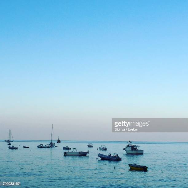 Boats In Calm Blue Sea Against Clear Sky