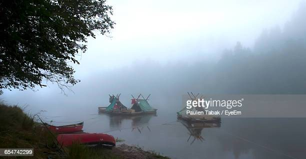 boats in calm misty lake - paulien tabak stock pictures, royalty-free photos & images