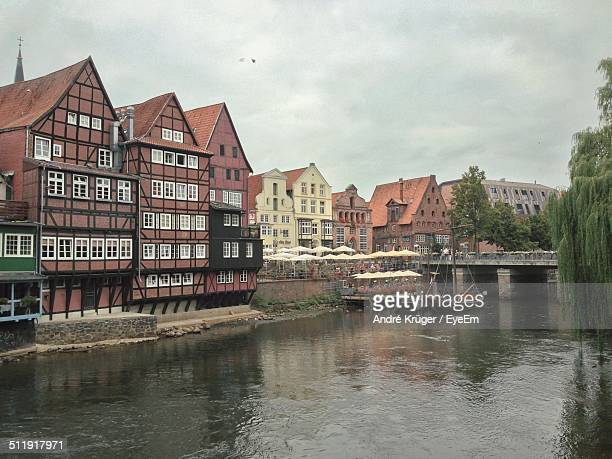 boats in canal along buildings - lüneburg stock photos and pictures