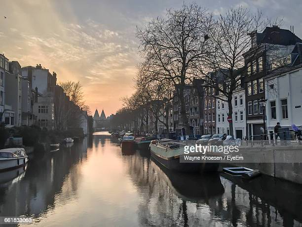 Boats In Canal Amidst Buildings Against Cloudy Sky At Dusk