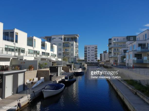 Boats In Canal Amidst Buildings In City Against Clear Blue Sky