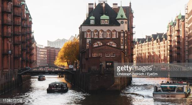 boats in canal amidst buildings in city against sky - waterfront stock pictures, royalty-free photos & images
