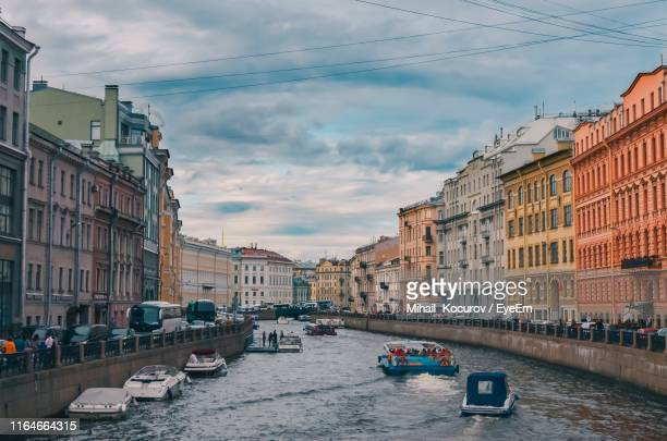 boats in canal amidst buildings in city against sky - st. petersburg russia stock pictures, royalty-free photos & images