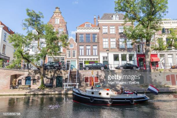 boats in canal by buildings in city - utrecht stock-fotos und bilder