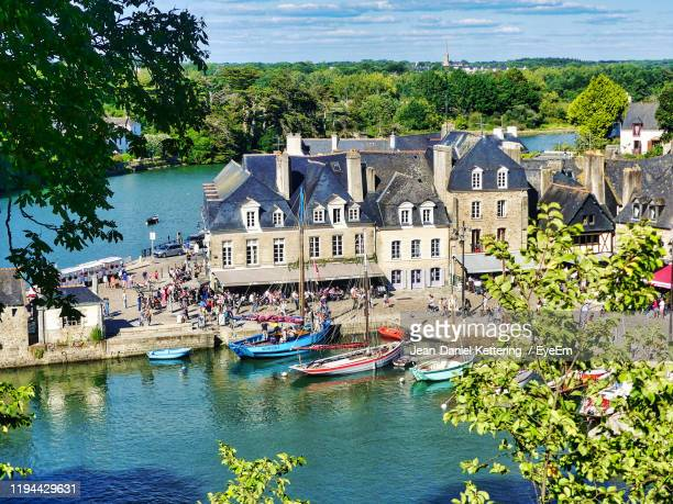 boats in canal by buildings in city - golfe du morbihan photos et images de collection