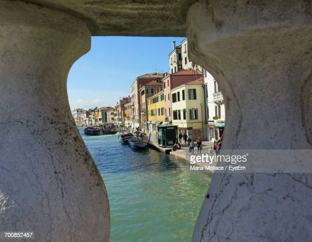 boats in canal by buildings seen through stone railing - venice foto e immagini stock