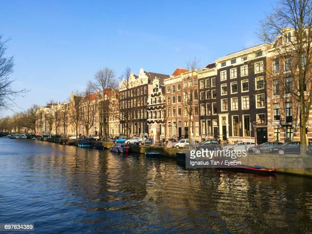 boats in canal with buildings in background - ignatius tan stock photos and pictures