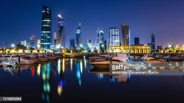 boats in harbor against illuminated buildings in city at night - kuwait city stock photos and pictures
