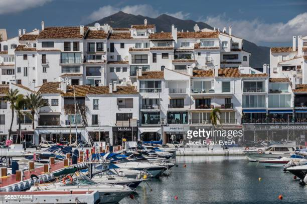 boats in harbor by buildings in city - マルベーリャ ストックフォトと画像