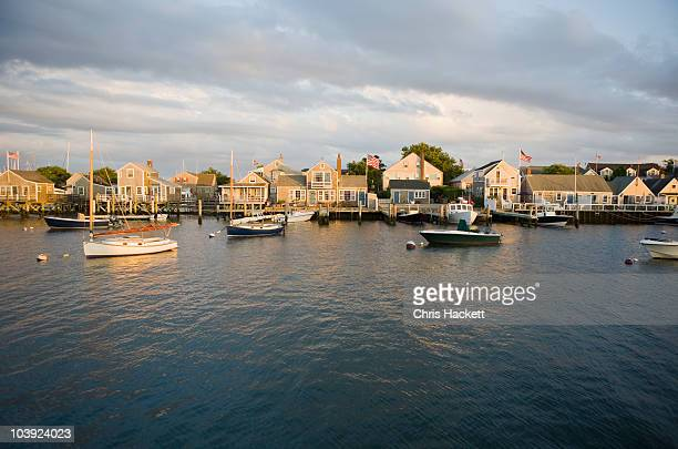 boats in harbor with village in background - nantucket stock pictures, royalty-free photos & images