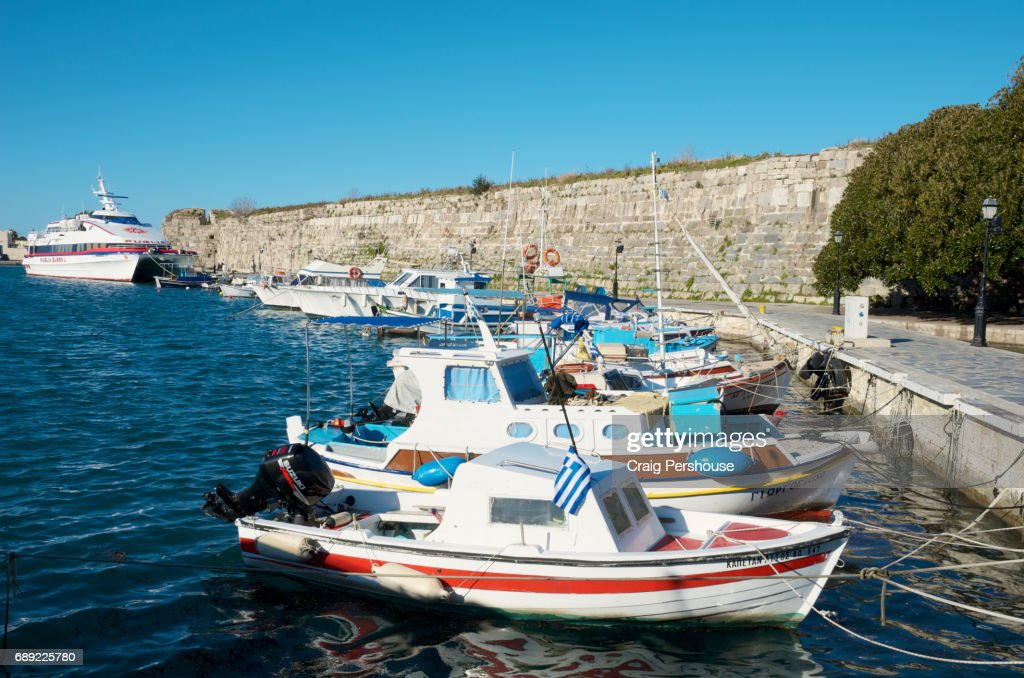 Boats in Kos Town Harbour before a wall of the Castle of the Knights. : Stock Photo