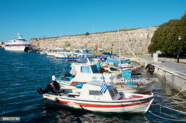Boats in Kos Town Harbour before a wall of the Castle of the Knights.