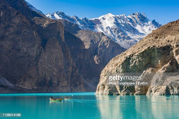 boats in lake against mountains and sky - gilgit stock pictures, royalty-free photos & images