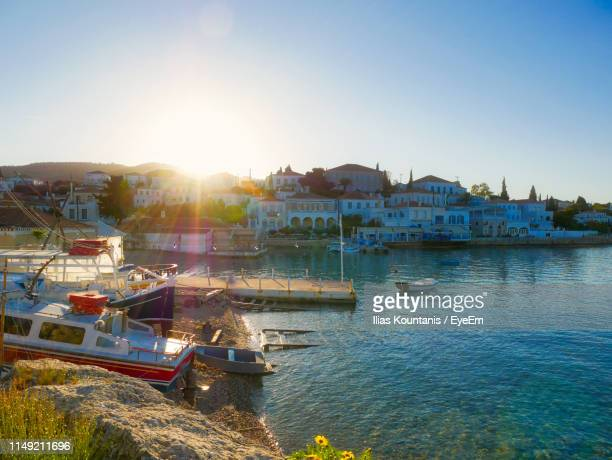 boats in marina at harbor against clear sky - spetses stock pictures, royalty-free photos & images