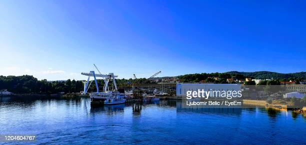 boats in river against clear blue sky - ljubomir belic stock pictures, royalty-free photos & images