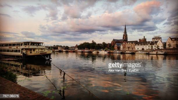 Boats In River Against Cloudy Sky