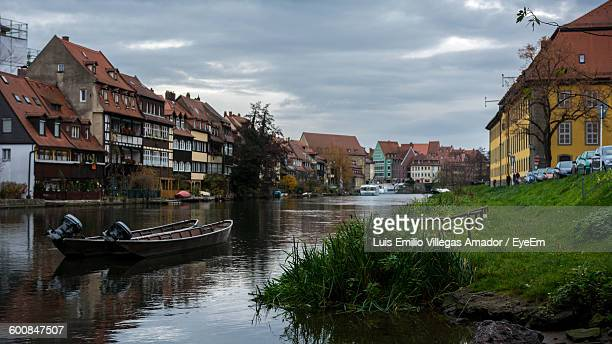 Boats In River Amidst Houses Against Sky