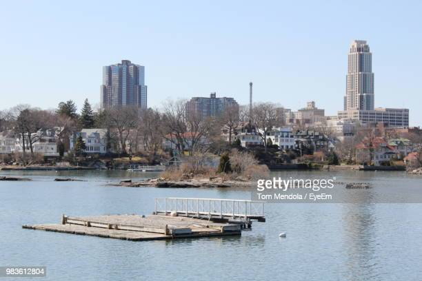 boats in river by buildings against sky in city - westchester county stock pictures, royalty-free photos & images