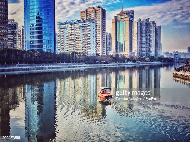 Boats In River By Cityscape Against Sky