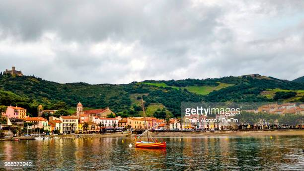 boats in river by townscape against sky - collioure photos et images de collection