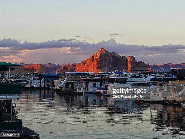 boats in river in front of town against sky during sunset - lake powell stock pictures, royalty-free photos & images