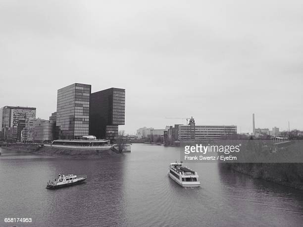 boats in river with city in background - frank swertz stockfoto's en -beelden