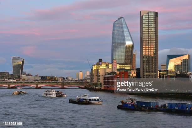 boats in sea against modern buildings in city against sky - passenger craft stock pictures, royalty-free photos & images