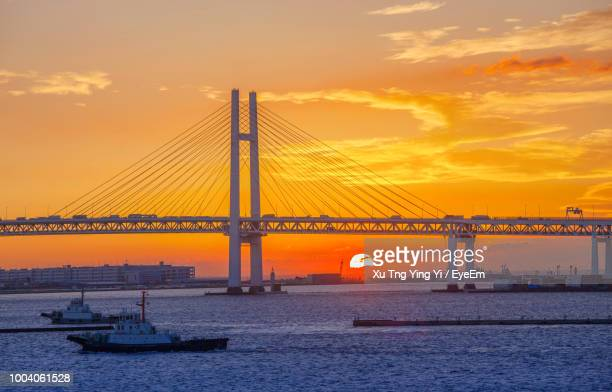 Boats In Sea With Cable-Stayed Bridge Against Orange Sky During Sunset