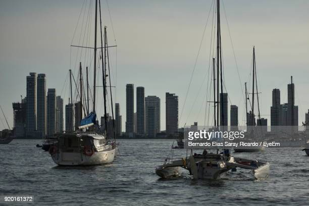 Boats In Sea With City In Background