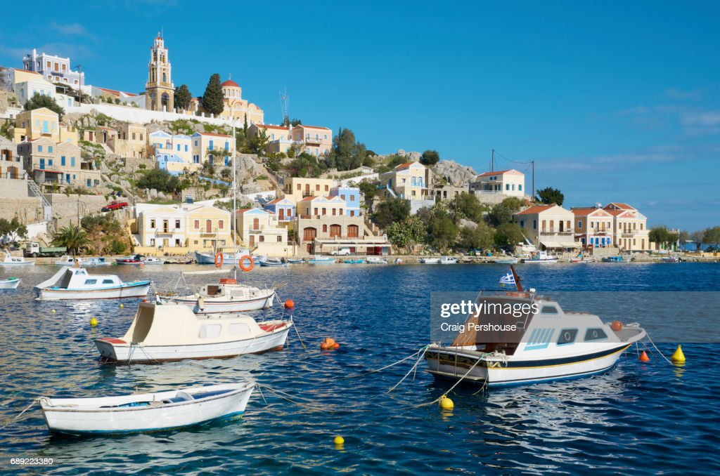 Boats in Symi Harbour before pastel-coloured houses and Ekklisia Evaggelistria (Annunciation Church). : Stock Photo