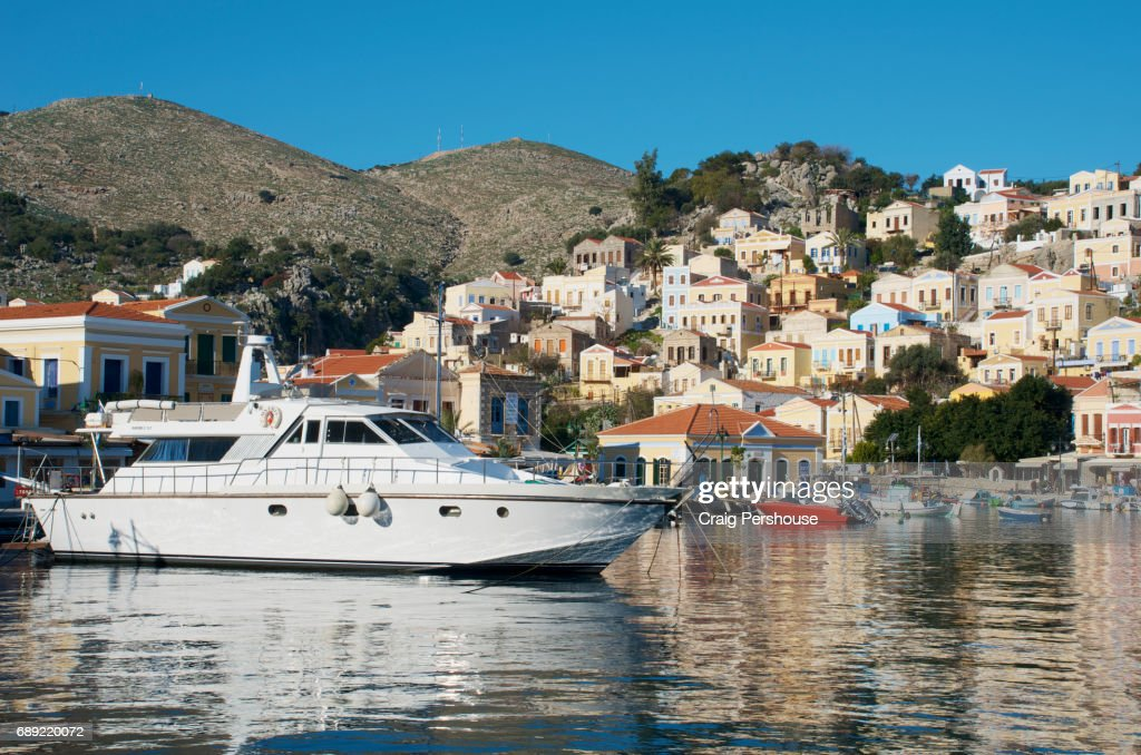 Boats in Symi Harbour before pastel-coloured houses. : Stock Photo